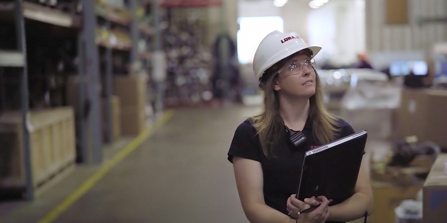 woman with hardhat in warehouse